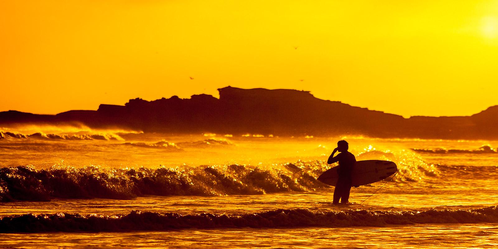 Wellenreiter, der mit Surfbrett in der Hand aufs Meer hinausblickt - Deaf IT Konferenz #event #deafit
